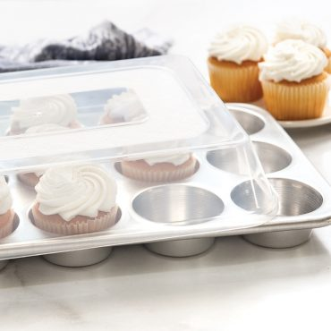 Lid on muffin pan filled with vanilla cupcakes, plated cupcakes in background