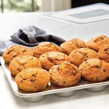 Baked chocolate chip muffins in muffin pan, lid in background