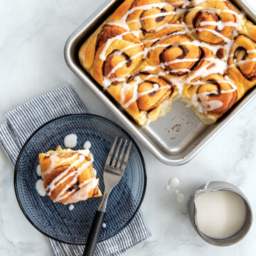 """Cinnamon rolls baked in 9"""" Square Cake Pan, one cut and plated"""
