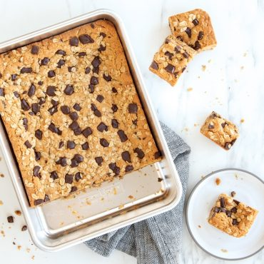 Oatmeal chocolate chip bars in rectangular pan, pieces cut on plate