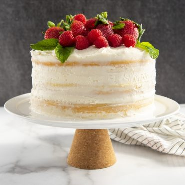 Glazed vanilla layered caked cake topped with raspberries and mint leaves, on a cake stand