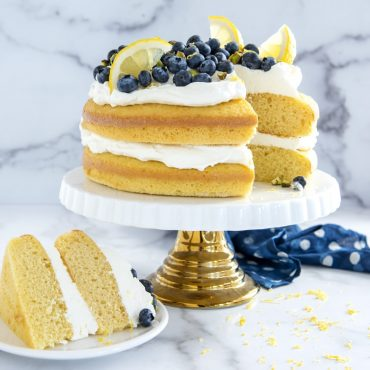 2 Layered cake with frosting in between layers and on top with fresh blueberries and lemon slices, one cut piece.