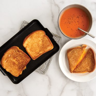 Two cooked grilled cheeses on mini griddle, one grilled cheese plated with tomato soup