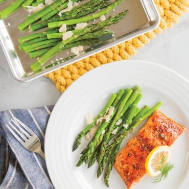 Roasted asparagus with cheese in pan, plated baked salmon, asparagus, lemon slice