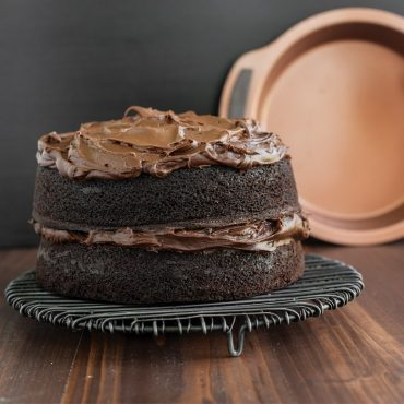 Baked two layer chocolate cake with chocolate frosting on rack, copper pan in background