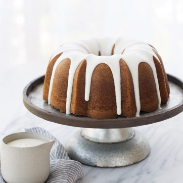 Glazed baked Bundt on a silver cake stand, glaze container on surface