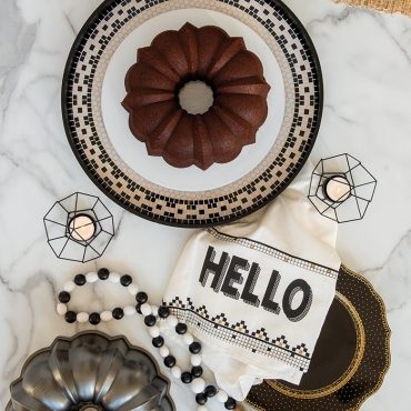 Baked chocolate Bundt on plate with product and props in background