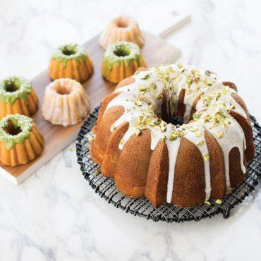 Baked and glazed Bundt® cake on cooling rack, with mini baked glazed cakelets on tray