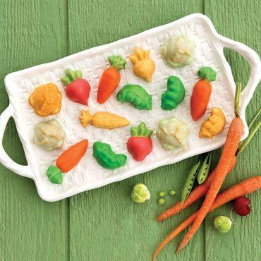 Glazed veggie cakelets on basket design platter, fresh vegetables such as carrots, pea pods and radishes on green wooden surface.