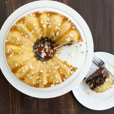 Chocoflan baked in Bundt springform pan on plate with caramel, cut piece on plate