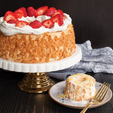 Large baked angelfood cake on cake stand with whipped cream and fresh strawberry garnish, mini cake with glaze and lemon zest on plate with fork