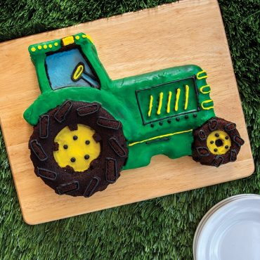 Baked tractor cake decorated in green and yellow frosting on wooden board on a fake grass surface. Plates in scene