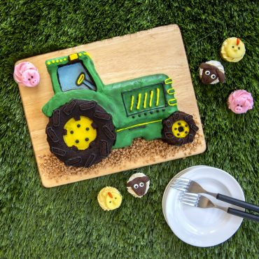 Baked and decorated tractor cake with animal cupcakes around (pigs, sheep, and chicks)
