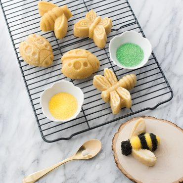 Various bug cakes on cooling rack with colored sugar sprinkles, decorated bee cake on plate
