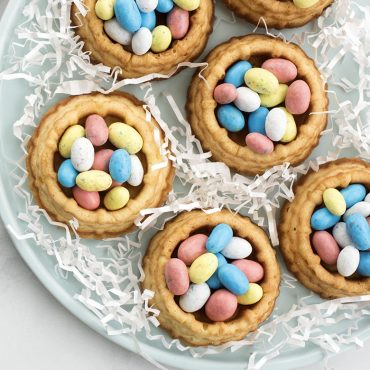 baked basket cakes filled with Easter egg candy on decorated plate, cake pan in background