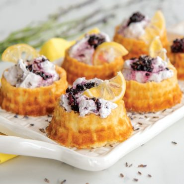 Baked basket cakes filled with whipped cream and blackberries, lemon slice garnish, on tray