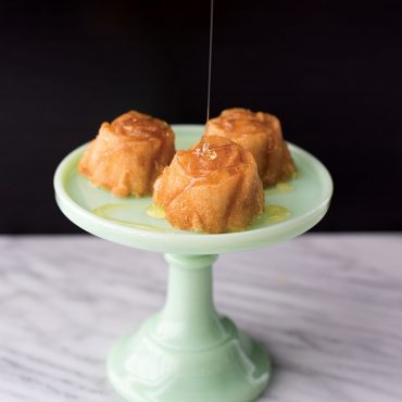 Three baked vanilla rose cakes in cake stand, drizzled with honey
