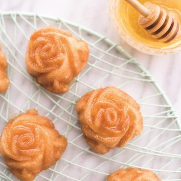 Baked rose cakes with honey glaze, on cooling rack, honey in bowl with dipper
