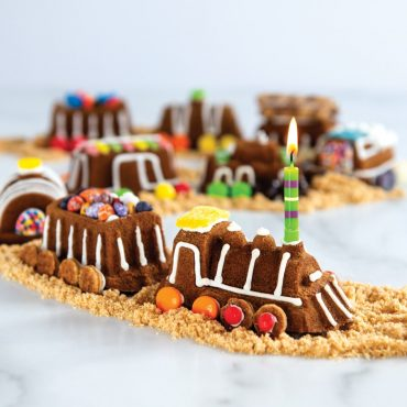 Baked train cake decorated in assortment of candies, formed in a train line on a brown sugar track.