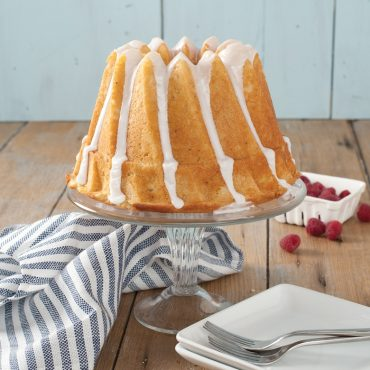 Baked Bundt cake with white glaze on cake stand, fresh raspberries in container