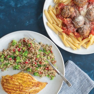 Plate with grilled chicken and quinoa salad, plate with pasta, spaghetti sauce and meatballs