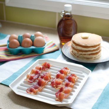 Microwave cooked bacon on bacon tray on table, stack of cooked pancakes on plate, syrup, brown eggs in carton