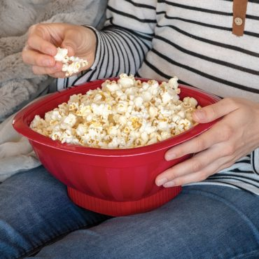 Popped popcorn in Pro Pop Popper on person's lap, taking handful