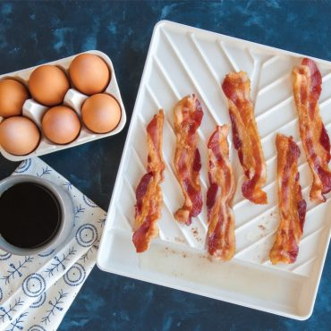 Top view microwave cooked bacon on tray, brown eggs in carton, cup of coffee