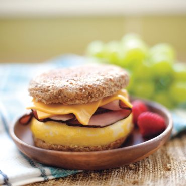 whole grain English muffin with cooked egg, cheese, Canadian bacon on plate
