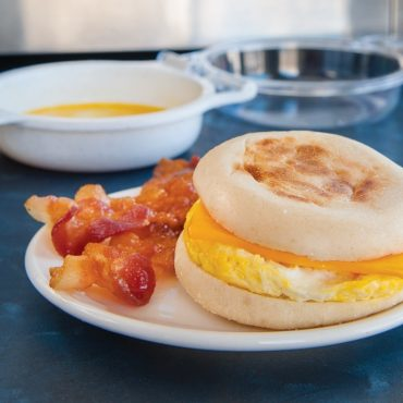 Microwaved egg with cheese on split English muffin, with cooked bacon on plate