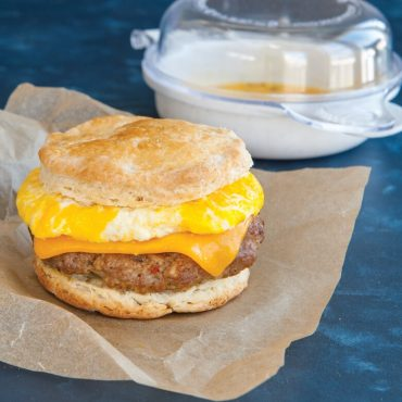 Microwaved egg with cheese and sausage patty on split biscuit set on parchment paper wrapper, product in background.