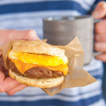 Hand holding microwaved egg with cheese and sausage patty on split biscuit set in parchment paper wrapper, on-the-go meal