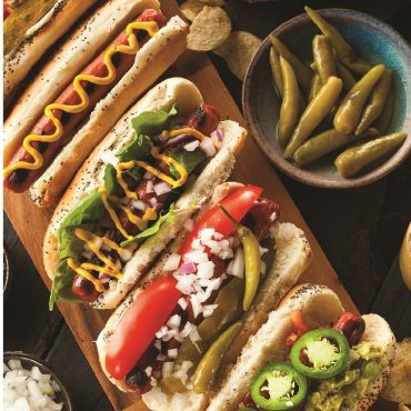 Variety of hot dogs and condiment in bus on serving platter