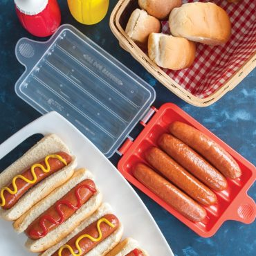 Microwaved hot dogs on buns with ketchup and mustard on serving plate, Hot Dog Steamer on the side open with cooked hot dogs