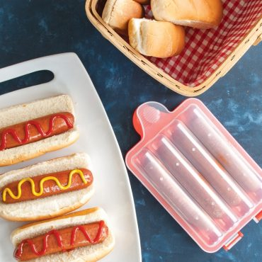 Microwaved hot dogs on buns with ketchup and mustard on serving plate, Hot Dog Steamer on the side with cooked hot dogs inside