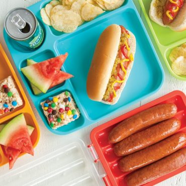 Microwaved brats in open steamer, picnic plate with brat, condiments in bun, watermelon wedges, rice krispy bar, chips