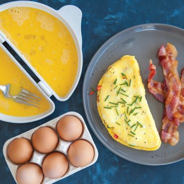 Uncooked egg in open omelet pan, brown eggs in tray, pate with cooked omelet and bacon strips on plate