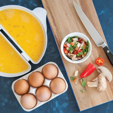 Uncooked egg in open omelet pan, brown eggs in tray, chopped peppers and mushrooms on cutting board with knife