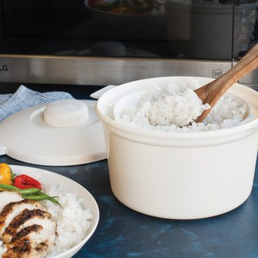 Open rice cooker with cooked rice, plate with cooked rice, sliced chicken, vegetable