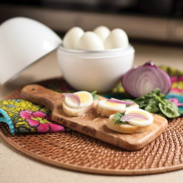 Sliced hard boiled eggs on cutting board with onion and basil  garnish