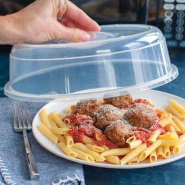 Microwave cover being removed from plate of pasta, meatballs and sauce