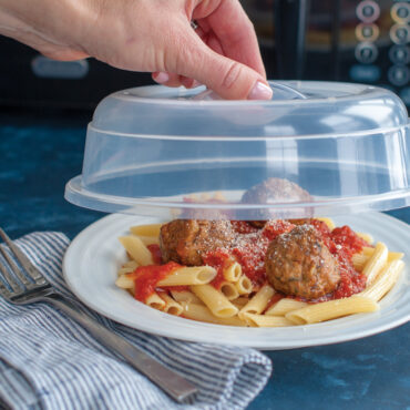 Hand holding spatter cover over plate of food, microwave in background