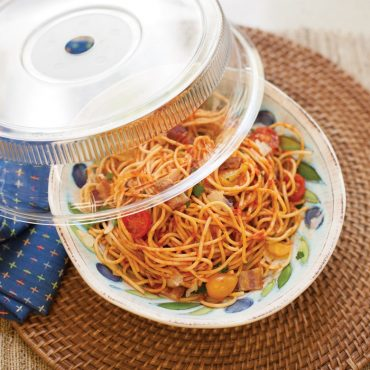 Deluxe plate cover beside plate of cooked spaghetti and vegetables