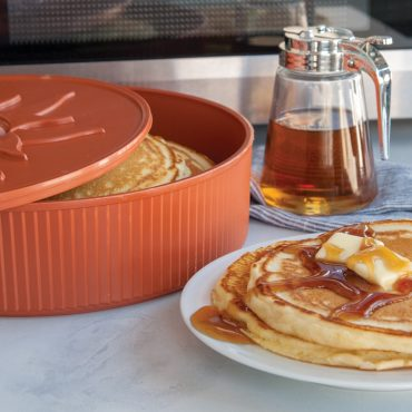 Warmer with cooked pancakes, pancakes on plate with syrup and butter, syrup container