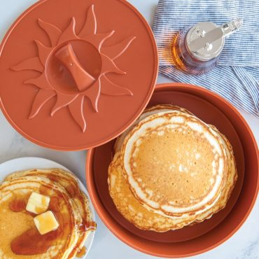 Overhead large pancakes in Pancake warmer, plate of pancakes and syrup next to container