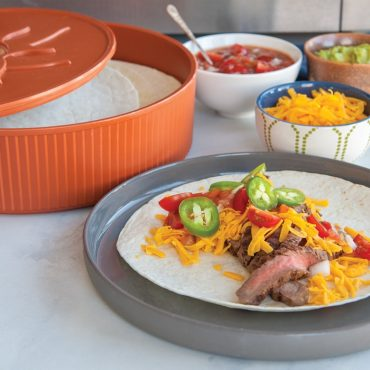 Open warmer with tortillas, tortilla on plate with sliced beef, grated cheese, chopped tomatoes and jalapeno peppers