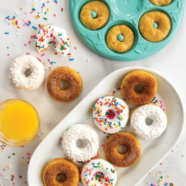 Platter filled with microwave cooked donuts topped with cinnamon sugar and white glaze, colorful sprinkles.