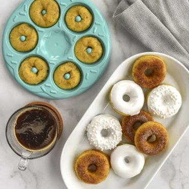 Donut Bites Pan filled with raw batter, next to plate of decorated cooked donuts, cup of coffee on the side.