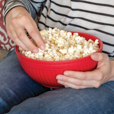 Person with bowl of cooked popcorn