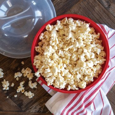 Overhead close-up of bowl with popcorn, red and white dish towel